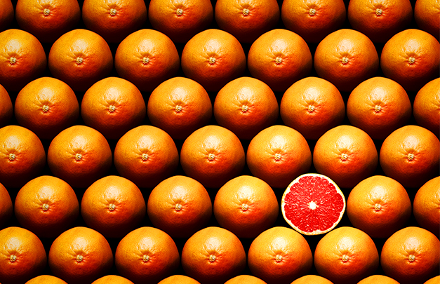 many rows of whole grapefruits with one sliced grapefruit