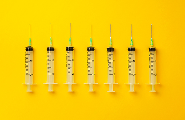 line of syringes against a yellow background